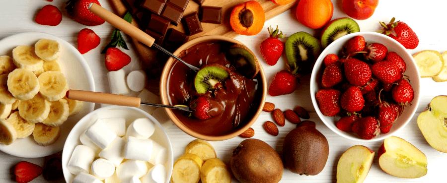 Закуски для шоколадного фондю на столе вокруг фондюшницы