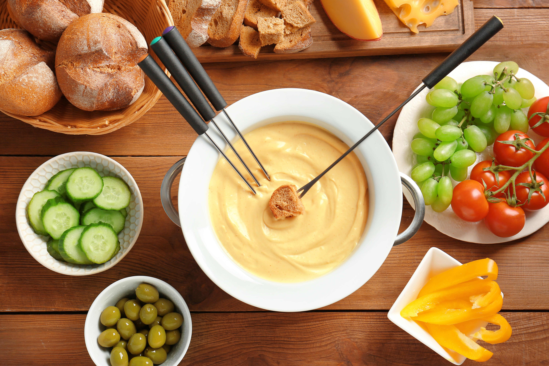 Сырное фондю посредине и различные добавки, которые подчеркнут и дополнят его вкус