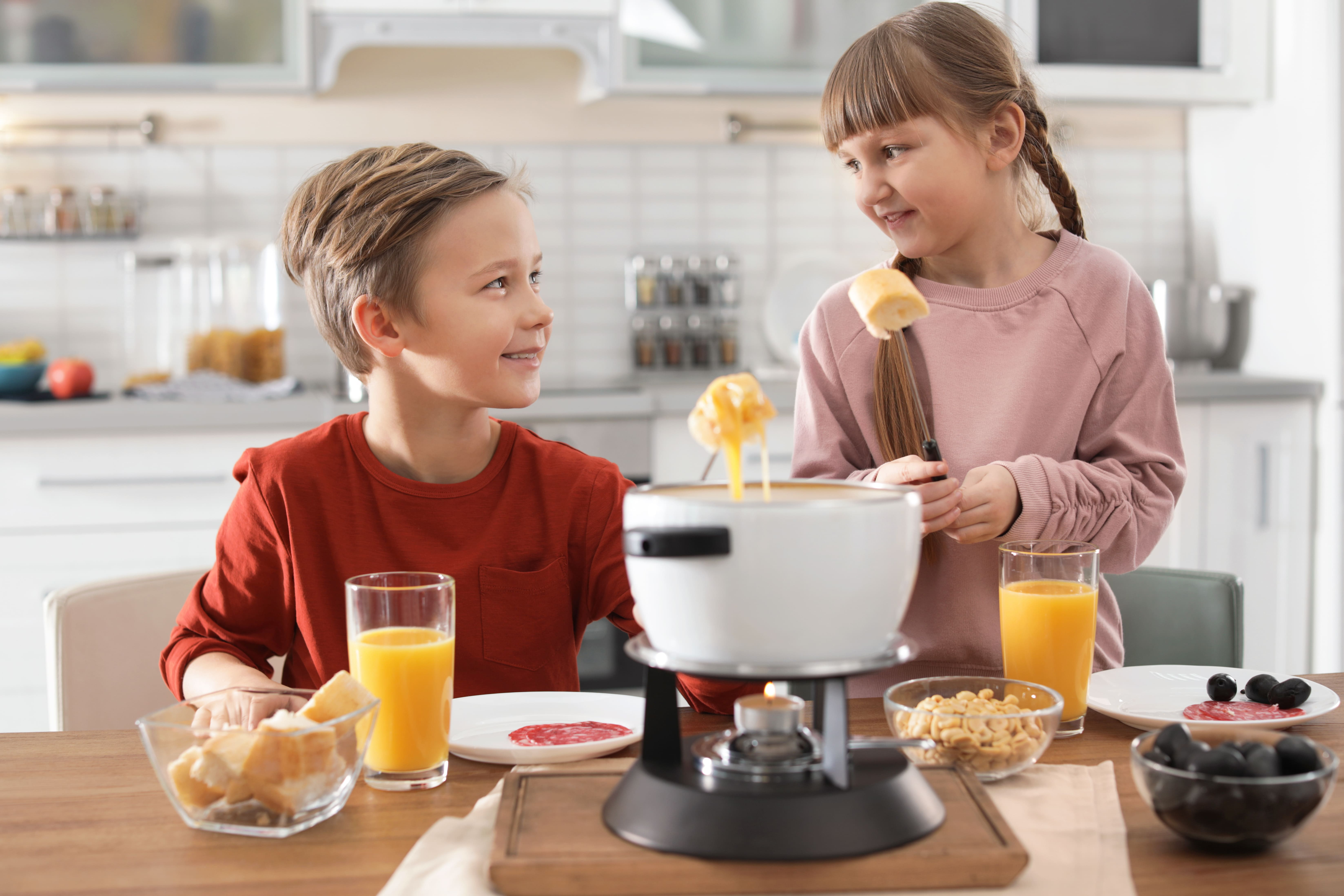 Дети за поеданием сырного фондю, которое готовится без вина
